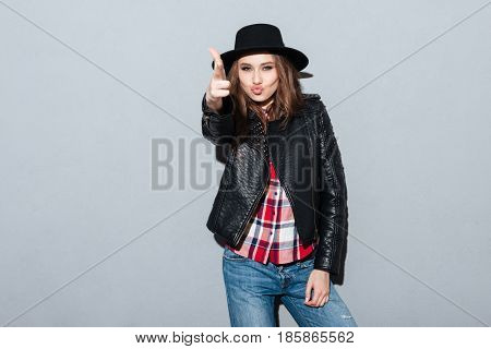 Portrait of a pretty young woman in hat and leather jacket shoots from improvised gun isolated over gray background