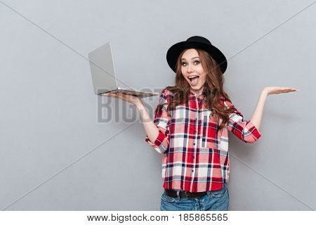 Portrait of a happy excited teenager girl holding laptop and copyspace on her palms isolated over gray background
