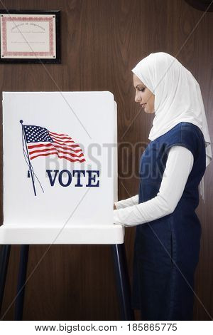 Middle Eastern voter voting in polling place