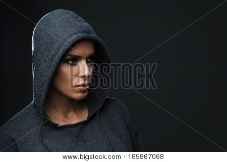 Portrait of a beautiful sports girl with brown eyes, wearing sportswear with a hood on her head, on a dark background.