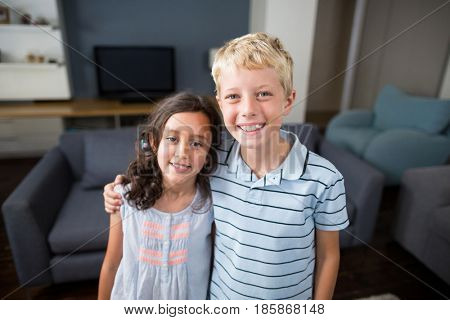 Portrait of siblings standing with arm around in living room at home