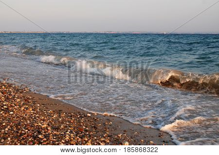 Waves on the beach at the sea. Changeable weather on summer vacation at sea