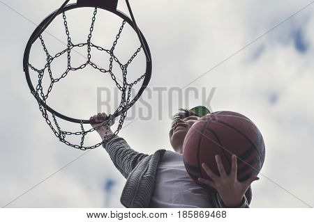 A little boy jumping and making goal playing streetball, basketball. Throws a basketball ball in the ring. The concept of sport