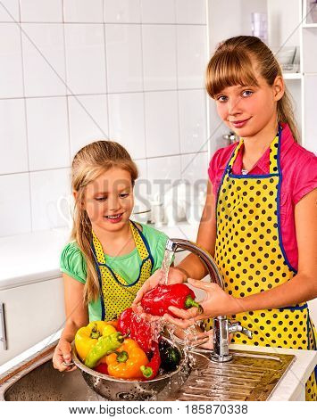 Fruit and vegetable wash of children on kitchen home. Girl washing vegetables under pouring water tap in colander sink indoor. Protection against bacteria and germs.