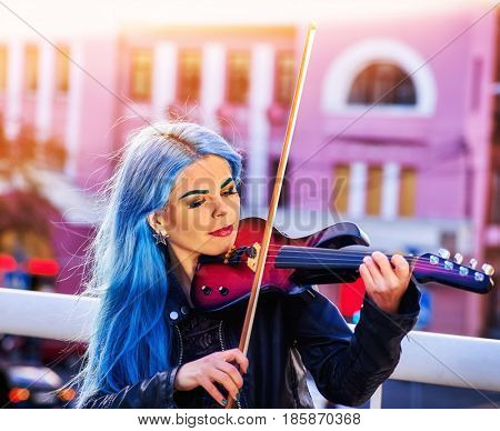 Playing viola woman perform music on violin in park outdoor. Girl with blue hairstyle and eyebrows performing jazz on city street . Girl image playing in game blue whale among teenagers In sun rays .