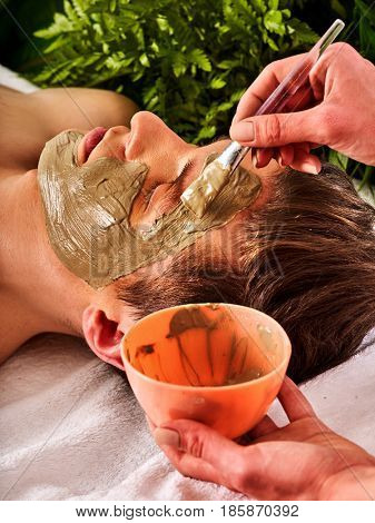 Mud facial mask of man in spa salon. Massage with clay full face. Girl on with therapy room. Man lying wooden spa bed. Beautician with bowl therapeutic procedure isolated background. Close-up of a man