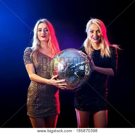 Dance party with group people dancing. Two women have fun in night club. Dark background and disco ball in hands of girls. Female are getting ready for erformance in nightclub.