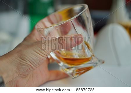 Male hand holding a whiskey glass with golden liquor as a symbol of drinking alcohol