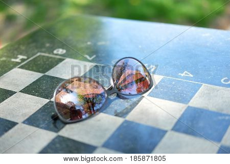 Checkerboard corner with sunglasses on it outdoors in summer. Mind game concept.