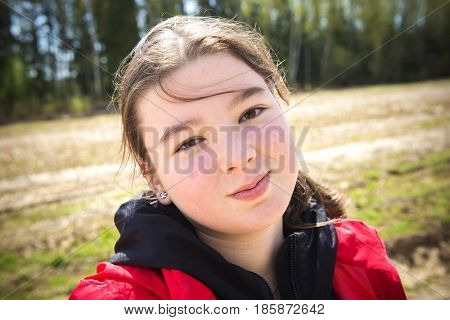 A teenage girl in a red vest walks in a spring forest