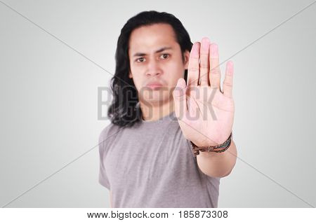 Photo image portrait of a cute handsome young Asian man with long hair showing stop gesture with angry facefocus on palm with blur face