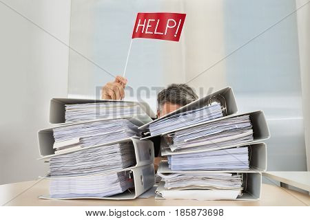 Stack Of Folders In Front Of Businessman Holding Red Flag With Help Text