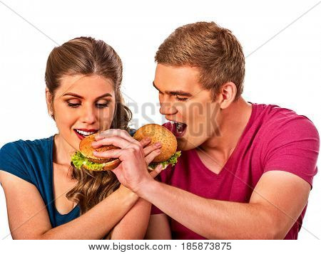 Couple eating fast food. Man and woman eat hamburger with ham. Friends holding two burder junk on white background isolated. People try to feed each other. Enamored people have breakfast together.