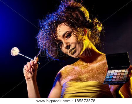 Visagiste woman with decorative cosmetics. Girl with curls holds eye shadow and brush on dark background. Golden powder on female bare shoulders on black background.