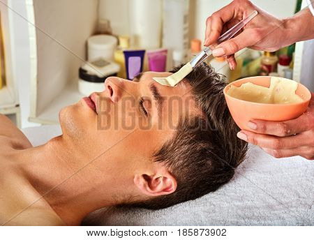 Mud facial mask of woman in spa salon. Massage with clay full face. Girl on with therapy room. Female lying wooden spa bed. Beautician with bowl therapeutic procedure isolated background. Anti-aging
