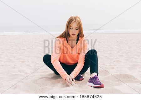 Beautiful red-haired girl sitting on the beach on a cloudy day