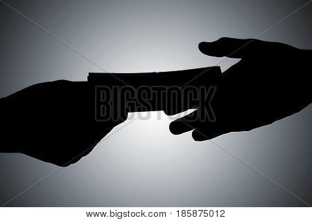 Silhouette Of Hands Giving Bribe Against Gray Background