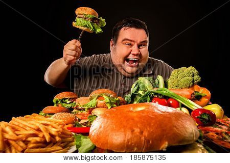 Diet fat man who makes choice between healthy and unhealthy food. Overweight male with hamburgers, french fries and vegetables trays trying to lose weight first time. Aggressive fat man who ended diet