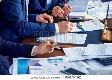 Business people office life of team people working with papers sitting table . Schemas and diagrams close up. Body part people in suits work in office and preparing for an economic project.