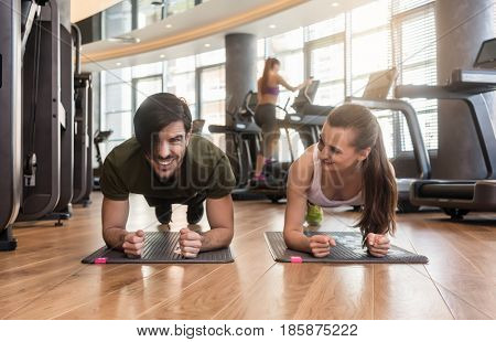 Cheerful young couple exercising forearm plank side by side on mats during workout in the interior of a modern fitness club