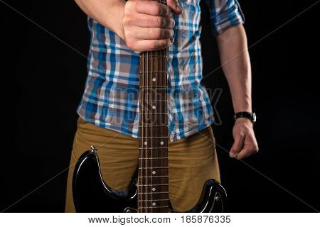 Music And Art. The Guitarist Holds An Electric Guitar In His Right Hand, On A Black Isolated Backgro