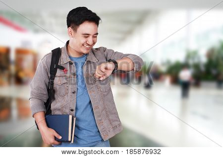 Time concept photo image portrait of a successful cute young Asian male student smiling and looking at his wristwatch half body close up portrait