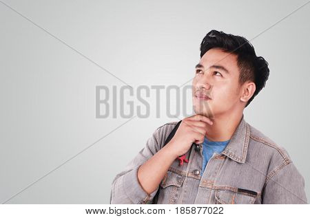 Photo image portrait of a cute young Asian male student standing looking up and thinking