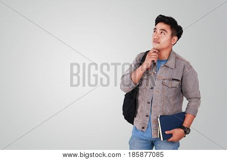 Photo image portrait of a cute young Asian male student standing looking up and thinking while holding some books