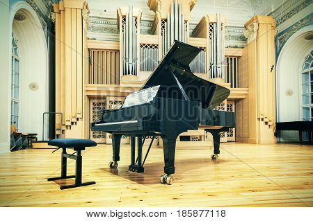 Big piano in concert hall with organ. Grand piano in hall.