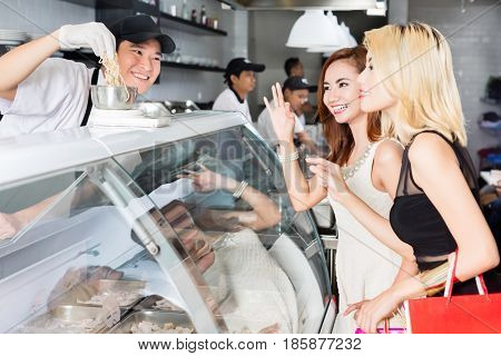 Smiling man assisting two stylish ladies as they purchase food at a deli counter smiling and gesturing as they make their choices