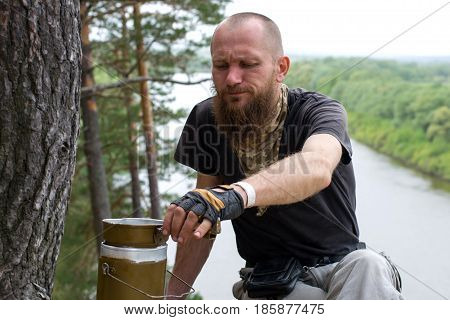 Traveler prepares for a gas burner food over cliff above the river