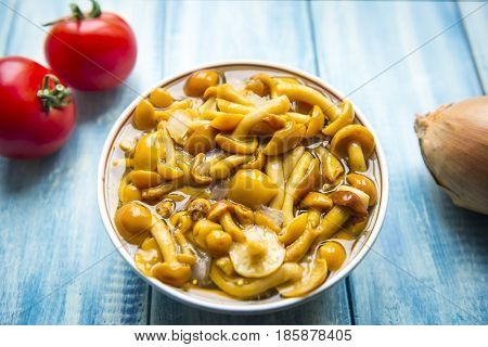 Marinated mushrooms (honey agarics) in a plate and fresh tomatoes