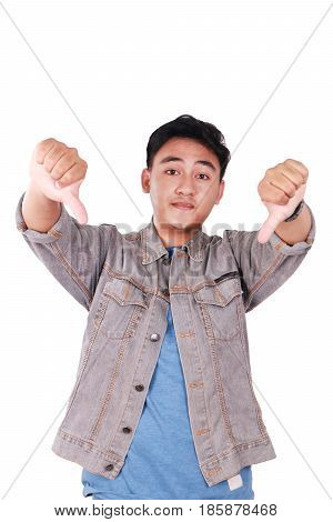 Photo image portrait of a cute young Asian man doing mocking gesture and showing two thumbs down isolated on white