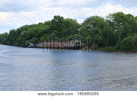 River with lonely rusty cargo ship dire straits among bushes and trees on summer day