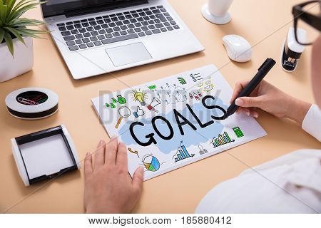 Close-up Of A Businessperson Drawing Goals Chart On Office Desk At Workplace