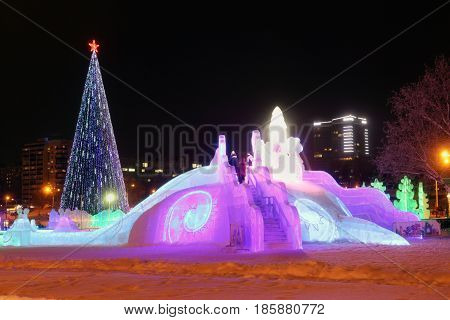 PERM RUSSIA - JAN 10 2017: Christmas tree and slide with illumination at evening Ice town of Perm in 2017 Ekosad - largest in Russia