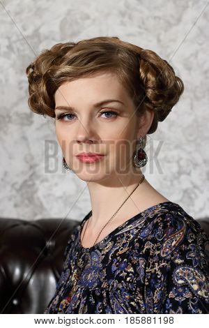 Beautiful young woman with hairdo and makeup poses on sofa in studio