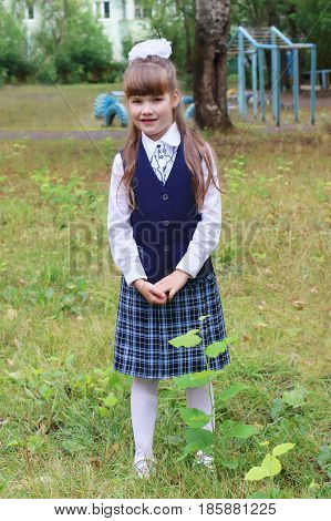Pretty little school girl in uniform poses in school park outdoor