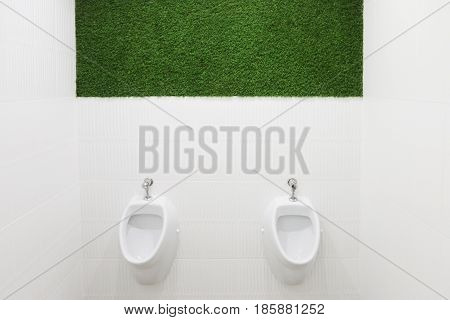 Two white urinals in empty male toilet with green lawn on wall