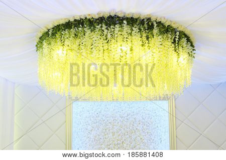 Yellow flowers hanging from ceiling wall with white artificial roses in hall for wedding