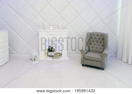 White room with decorative fireplace candles armchair soft walls