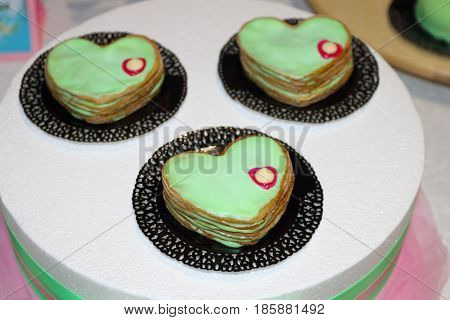 Sweet cakes green hearts are on plates on table during celebration