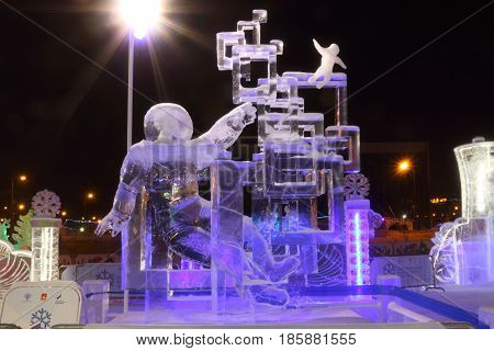 PERM RUSSIA - FEB 1 2017: Sculpture Space traveler at night Ice town of Perm in 2017 Ekosad - largest in Russia