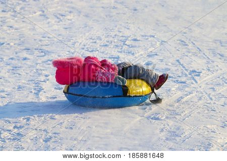 Little girl lies on snowtube down from hill at sunny winter day