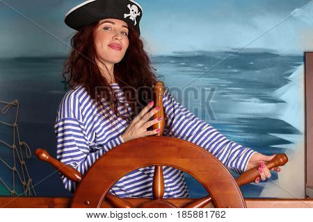 Dark-haired girll with a beautiful smile in a vest and a pirate hat holding the steering wheel