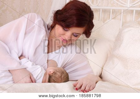 Happy young mother lying in bed and breast feed your baby and gently looks at her with all my love