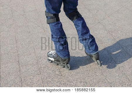 Young man in blue jeans roller-skates in the city with protective knee pads