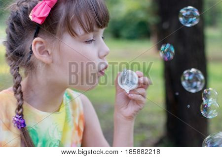 Little girl with cute pigtails and a sundress the color blow bubbles on a warm day