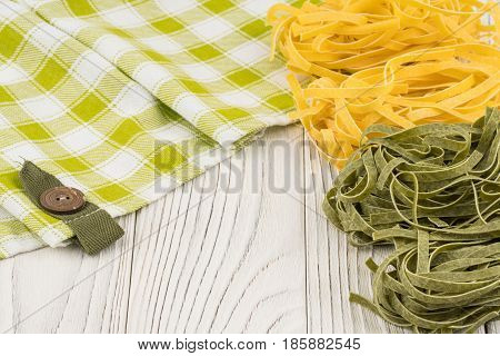 Raw green and yellow pasta on an old white wooden table. Selective focus.