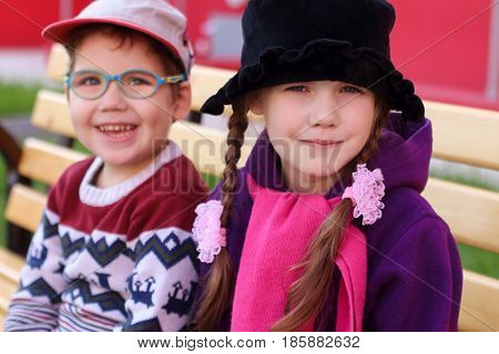 Beautiful cheerful children boy and girl in bright clothes sitting on bench focus on girl